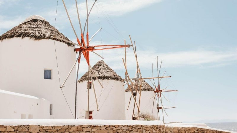 traditional greek windmills in a greek island hopping route