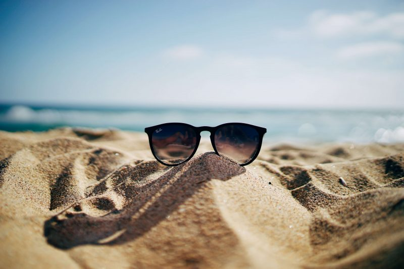 a pair of sunglasses for sailing sat on a beach with the sea behind