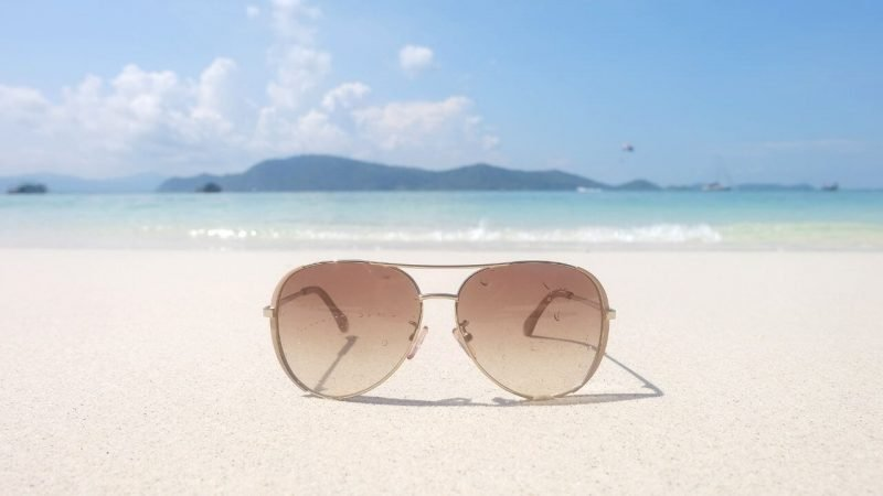 a pair of sunglasses for sailing lying on the beach in the sunshine