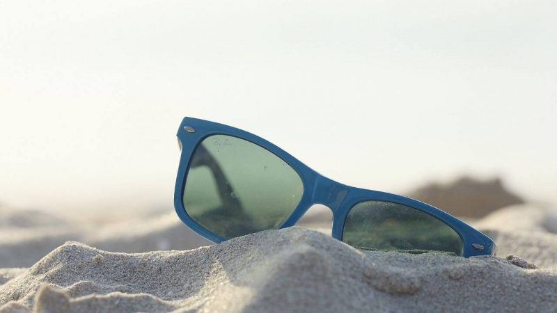 a pair of sunglasses for sailing lying on their side on the beach