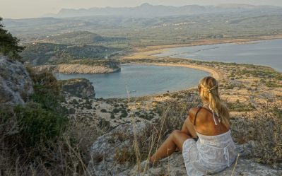 a girl sat looking over a beautiful view of her sailboat from the top of a castle in greece